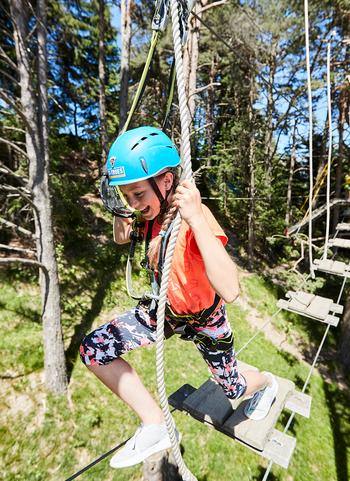 Mädchen springt von einer Hängebrücke auf eine Plattform im Waldseilpark